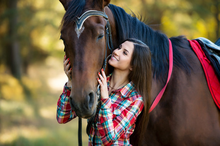 beautiful long hair young woman posing with a horse outdoor Stock Photo