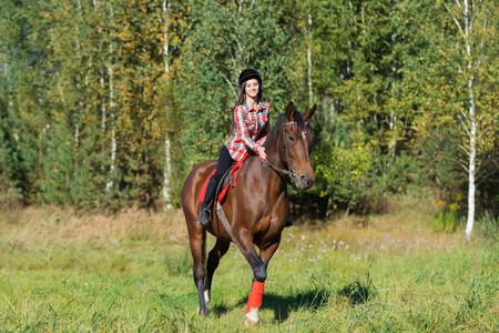 beautiful long hair young woman riding a horse outdoor
