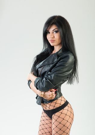 Portrait of biker girl on white background in black leather jacket and fishnet pantyhose. Brunette with make-up and long hair
