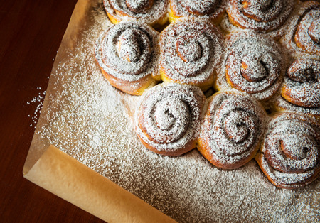 Sweet buns with Powdered sugar on paper. Small DOF