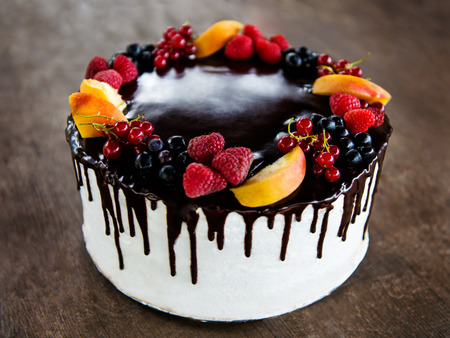 Chocolate cake with natural fruits on rustic wooden background. Small DOF.