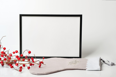 Christmas composition. Black frame and christmas sock with branches with red berries on white background. Front view, mock up, copy space, square, flat lay, for congratulations   Stock Photo
