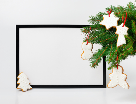 Christmas composition. Black frame and  branches christmas tree with gingerbreads on white background. Front view, mock up, copy space, square, flat lay, for congratulations
