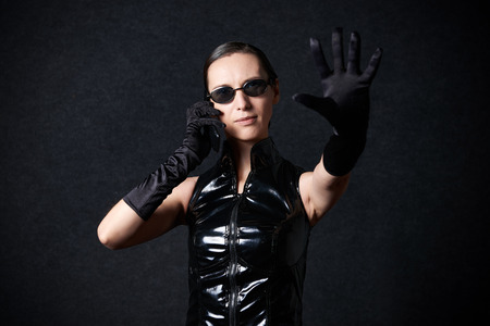 MINSK, BELARUS - NOVEMBER 03, 2018: UniСon Convention & Game Expo Minsk 2018. Cosplayer young woman as Trinity from Matrix shoot on black background in photo zone Editorial