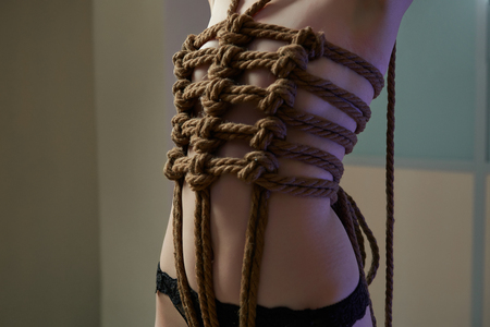 Young woman in black lingerie bound with a rope in Japanese technique shibari. Violence concept 写真素材