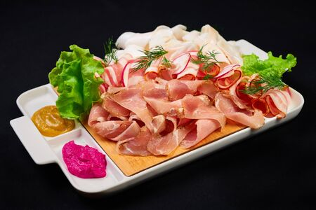 meat and sowbelly set. pub, restaurant, bar food concept. meat appetizers set with meat, sowbelly, tomatoes cherry, souses and fresh greens. Stock Photo
