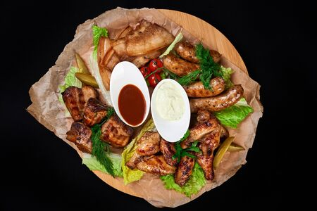 meat and snack set. pub, restaurant, bar food concept. meat appetizers set with grill chicken, sausages, tomatoes cherry, souses and fresh greens. Stock Photo - 128399616
