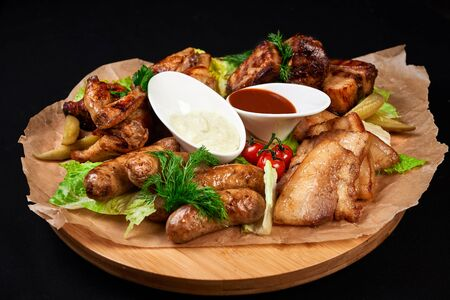 meat and snack set. pub, restaurant, bar food concept. meat appetizers set with grill chicken, sausages, tomatoes cherry, souses and fresh greens. Stock Photo - 128399617