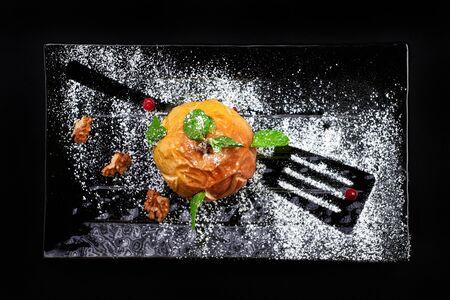 Gourmet Baked Apple. Autumn dessert on black background with sugar, mint, walnut Stock Photo
