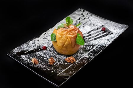 Gourmet Baked Apple. Autumn dessert on black background with sugar, mint, walnut Stock Photo - 128399621