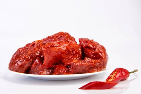 raw meat marinated in spicy sauce close-up, isolated on white background with slices pepper Stock Photo