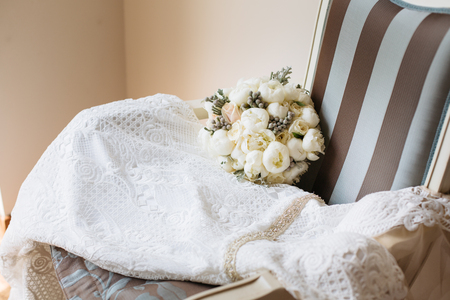 Bridal dress with bouquet on vintage striped chair. Bridal room interior. Wedding style.
