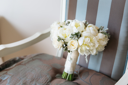 Wedding rustic bouquet on vintage striped chair. Bridal room interior. Stock Photo
