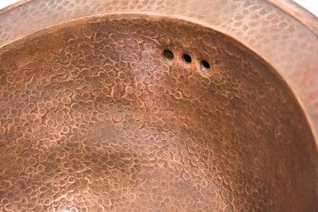 Detail of copper round sink. Brown copper sink in retro style. Antique sink for home. Macro shooting.