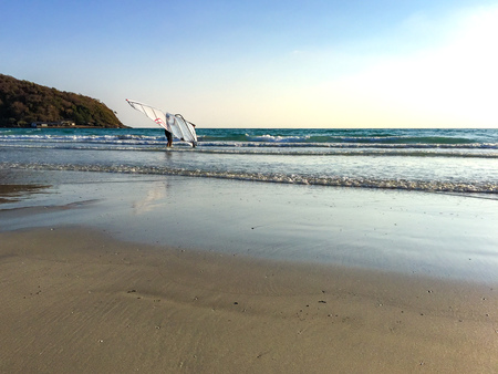 One man lifting the windsurf over his head. Trying to play windsurf in the blue sea. Stock Photo