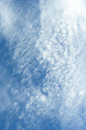 Bright blue sky and white wooly clouds background, bottom view , horizontal image. Reklamní fotografie