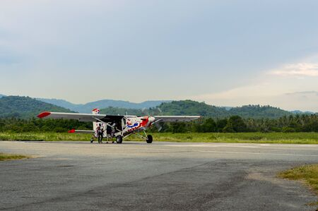 Small aircraft and parachutist was preparing boarding for sport parachuting. Green mountain and blue sky behind.