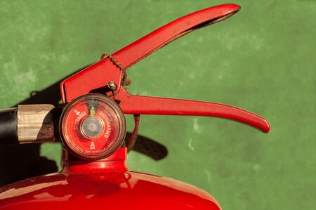 Fire extinguisher fully charged with gauge pressure on green concrete wall. Head section picture. Reklamní fotografie