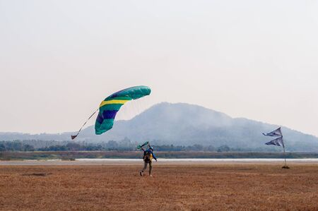 Parachutist landing beside runways on small airfield 版權商用圖片