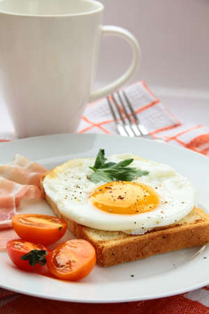 english breakfast: fried egg for breakfast with bacon and tomatoes