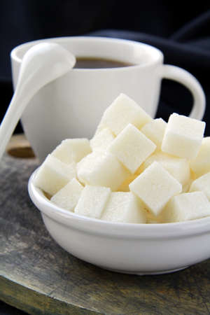 sugar: A cup of black coffee and refined sugar on a black background