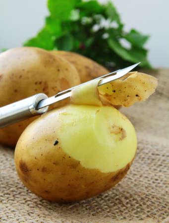 papas: patatas con un cuchillo para limpiar las verduras en el fondo natural Foto de archivo