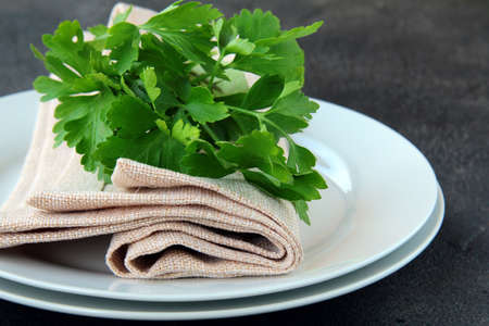 plates with a linen napkin and a sprig of parsley - organic menu photo