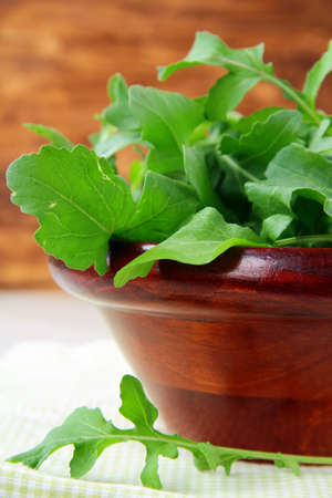 wooden cup with a green fresh arugula on the table Stock Photo - 9736265