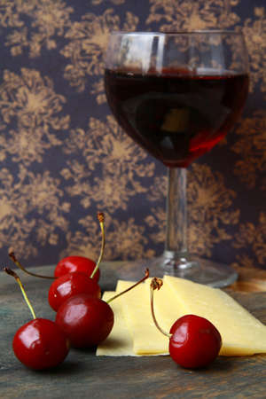 glass of red wine, cheese and cherry - a still life in vintage style photo