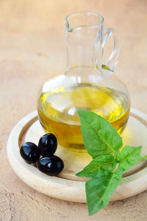 bottle of olive oil and a sprig of basil photo