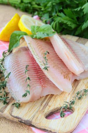 Filet de poisson cru frais aux herbes et d'épices sur une planche de cuisine