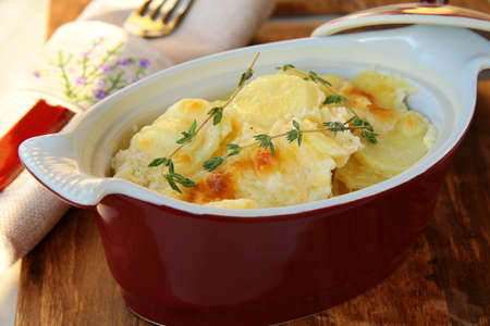scalloped: Potato gratin dauphinoise in the pan on rustic background