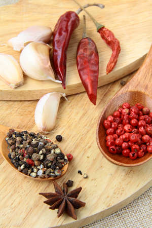 spices - red and black pepper, chili and garlic on a wooden background photo