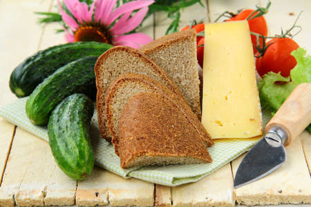 still life in a rustic style - cheese, tomatoes, cucumbers, rye bread on a wooden table photo