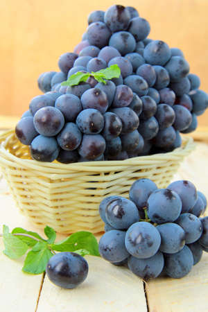 Brush black sweet grapes in a basket on wooden table Stock Photo - 9956088