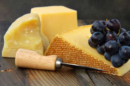 Cheese platter with grapes on a wooden black background photo