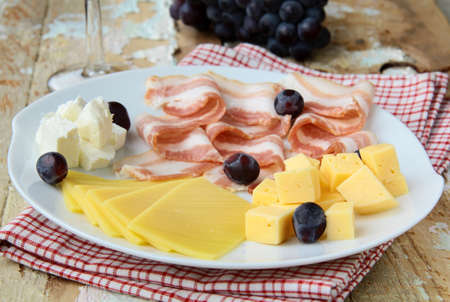 Snack cheese plate with grapes  and smoked bacon photo
