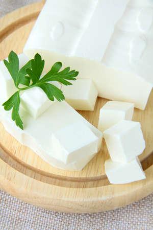 queso de cabra: queso feta en la tabla de cortar de madera Foto de archivo
