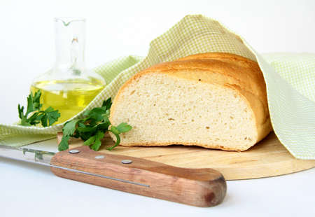 fresh white loaf of bread with a knife  and olive oil photo