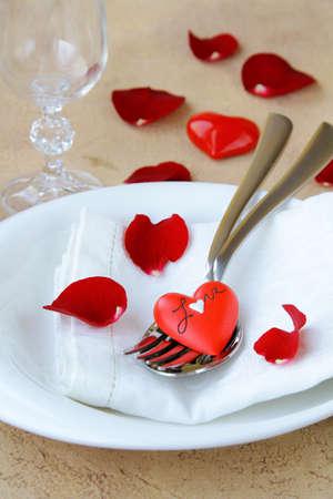 cena romantica: tavolo romantico con petali di rosa e cuori