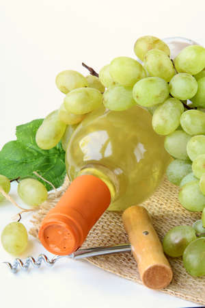 pervaded: bottle of white wine, grapes, and a corkscrew on a natural background