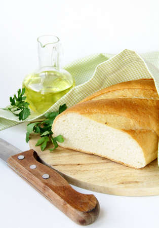 fresh white loaf of bread with a knife , olive oil , rustic style  photo