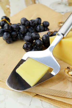 Cheese platter with grapes on a wooden  background photo
