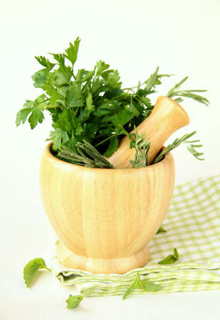 botanical remedy: herbs in wooden mortar with pestle