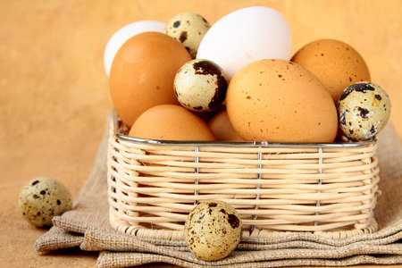 Group of brown and white hens eggs  in a wicker basket photo