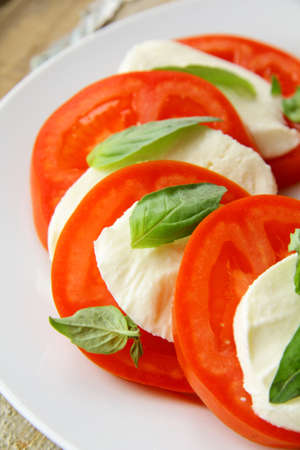 Traditional Italian Caprice salad tomato mozzarella cheese and basil  photo