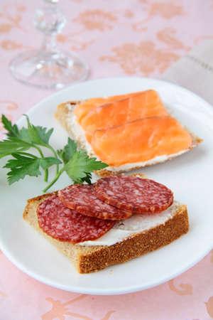 garnishing: canape sandwiches with salmon  and salami