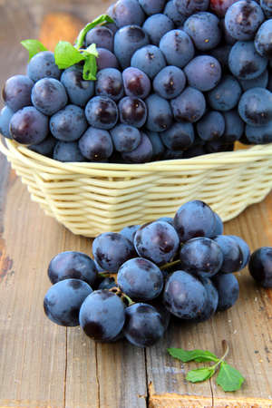black sweet grapes on wooden table  photo