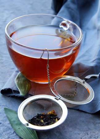 tea strainer with a fragrant black tea and cups in the background  photo