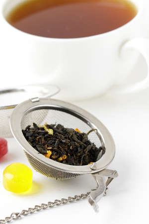 tea strainer with a fragrant black tea and cup in the background  photo